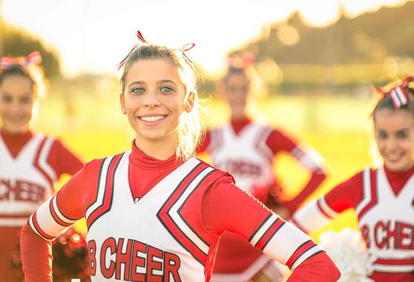 Portrait of an happy young cheerleader in action outdoors - Grou